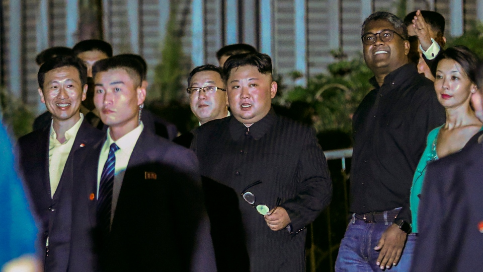 North Korea leader Kim Jong Un, centre, is escorted by his security delegation as he visits Marina Bay in Singapore, Monday, June 11, 2018, ahead of Kim's summit with U.S. President Donald Trump. (AP Photo/Yong Teck Lim)
