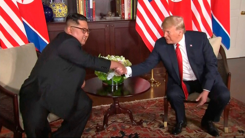 In this image made from video provided by Host Broadcaster Mediacorp Pte Ltd,, U.S. President Donald Trump and North Korean leader Kim Jong Un shake hands ahead of their meeting at Capella Hotel in Singapore, Tuesday, June 12, 2018. (Host Broadcaster Mediacorp Pte Ltd via AP)