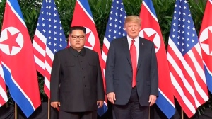 In this image made from video provided by Host Broadcaster Mediacorp Pte Ltd., U.S. President Donald Trump and North Korean leader Kim Jong Un pose together ahead of their meeting at Capella Hotel in Singapore, Tuesday, June 12, 2018. (Host Broadcaster Mediacorp Pte Ltd via AP)