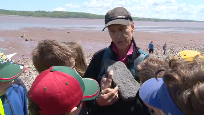 Chris Mansky tells a group of students what kind of fossil one of their classmates found at Blue Beach.