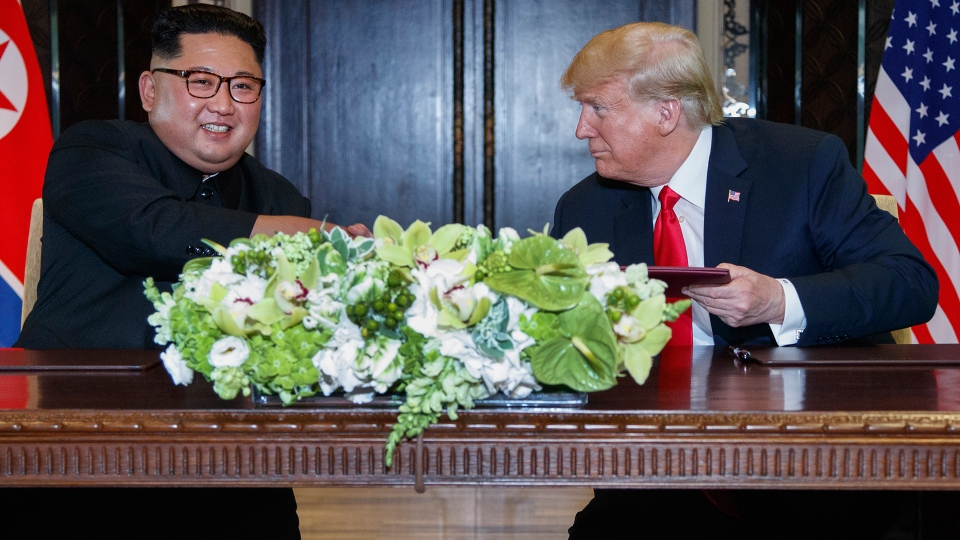 U.S. President Donald Trump looks at North Korea leader Kim Jong Un after their document singing at the Capella resort on Sentosa Island Tuesday, June 12, 2018 in Singapore. (AP / Evan Vucci)
