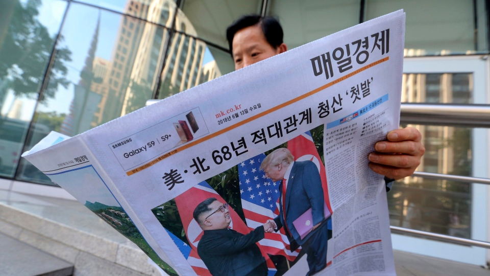 A man reads a newspaper reporting the summit between U.S. President Donald Trump and North Korean leader Kim Jong Un, at a newspaper distributing station in Seoul, South Korea, Tuesday, June 12, 2018. (AP Photo/Ahn Young-joon)