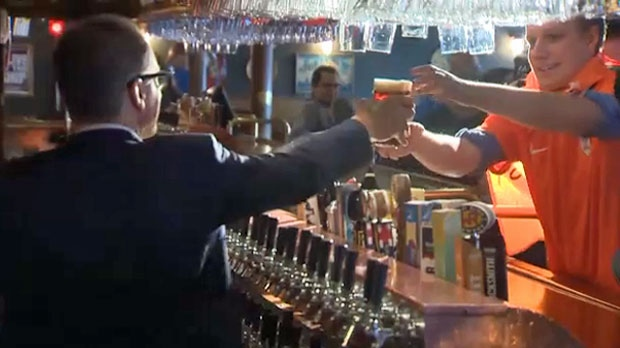 Finance minister Joe Ceci serves a pint to a Ship & Anchor customer after announcing that Alberta will allow bars to open early and serve alcohol during 2018 World Cup matches