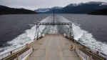 A crew member walks on the vehicle deck of the BC Ferries' vessel Island Sky while travelling on the waters off the Sunshine Coast, from Saltery Bay to Earls Cove, B.C., on Friday, March 17, 2017. (Darryl Dyck / THE CANADIAN PRESS)