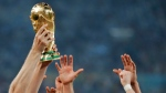 In this Sunday, July 13, 2014 file photo, German players reach out to touch the trophy after the World Cup final soccer match between Germany and Argentina at the Maracana Stadium in Rio de Janeiro, Brazil. (AP Photo/Matthias Schrader)