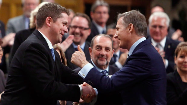 Conservative MP Maxime Bernier (right) gives the thumbs up to Conservative Leader Andrew Scheer in the House of Commons during Question Period on Parliament Hill in Ottawa, Monday, May 29, 2017. THE CANADIAN PRESS/Fred Chartrand