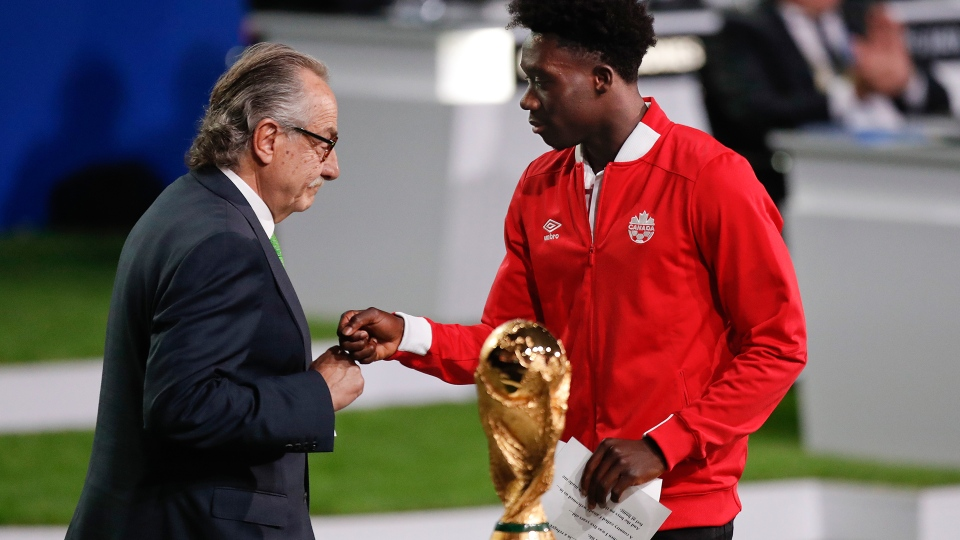 Decio de Maria, President of the Football Association of Mexico, left, and Canadian soccer player Alphonso Davies, right, present a joint United bid by Canada, Mexico and the United States to host the 2026 World Cup at the FIFA congress in Moscow, Russia, Wednesday, June 13, 2018. (AP / Pavel Golovkin)