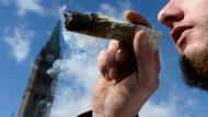 A man smokes a marijuana joint during the annual 4/20 marijuana celebration on Parliament Hill in Ottawa on April 20, 2018. THE CANADIAN PRESS/Justin Tang
