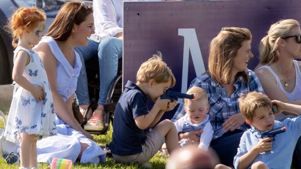 The Duchess of Cambridge, left, sits with Prince George and other unidentified spectators as they watch Prince William take part in the Maserati Royal Charity Polo Trophy at the Beaufort Polo Club, in Tetbury, England, Sunday June 10, 2018. (Steve Parsons/PA via AP)