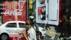 A woman is reflected in a Coca-Cola store window display as she drinks a Coke in Mexico City on Oct. 9, 2014. (AP Photo/Rebecca Blackwell)
