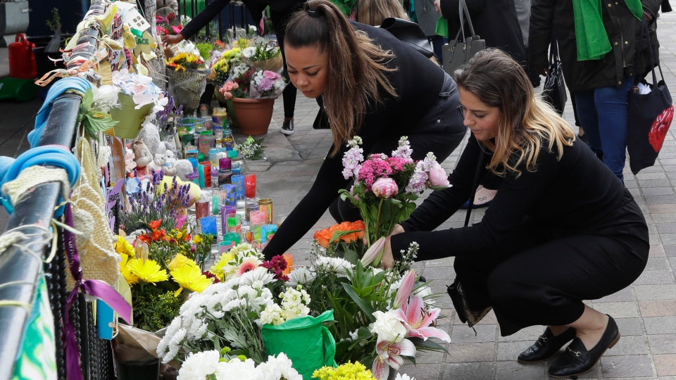 People place tributes outside Notting Hill Methodist Church in support for those affected by the massive fire in Grenfell Tower in London, Thursday, June 14, 2018. A year ago, London's Grenfell Tower high-rise was destroyed by a fire that killed 72 people. (AP Photo/Kirsty Wiggleworth)