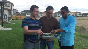 Rosewood residents look at a new building proposal that would interfere with plans for a road in front of their homes. Residents are petitioning against the plans. (Laura Woodward/CTV Saskatoon)
