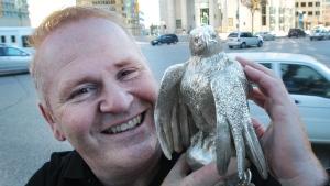 Ron Shore holds a solid silver eagle statue at Portage and Main St in Winnipeg Nov. 3, 2010. (THE CANADIAN PRESS/ Winnipeg Free Press - Joe Bryksa)