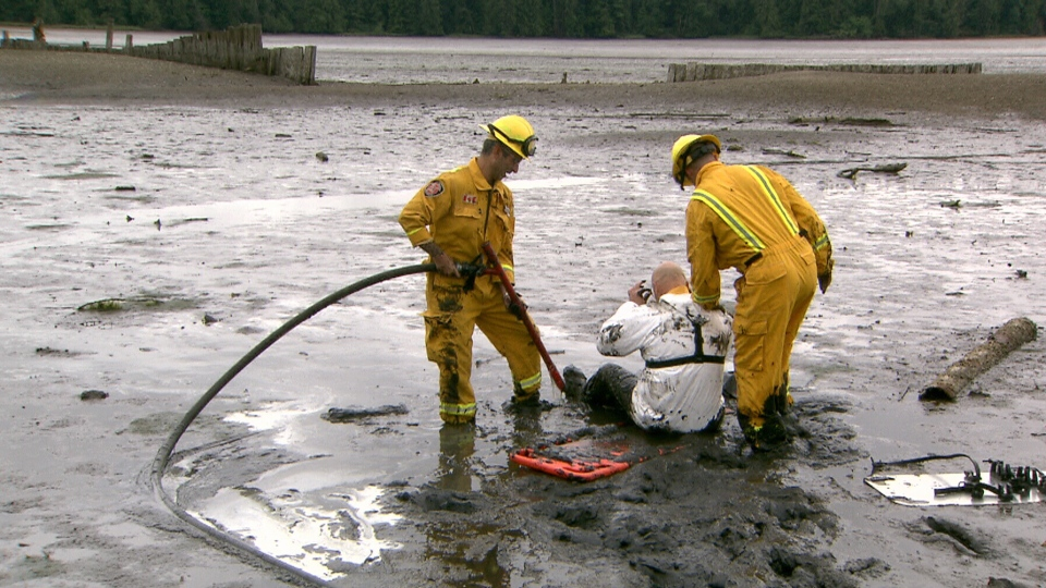 Port Moody firefighters are seen during a mud rescue exercise in the Burrard Inlet on June 14, 2018.