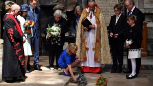 Lucy Hawking lays flowers as the ashes of her father, Stephen Hawking, are laid to rest during his memorial service at Westminster Abbey in London, Friday June 15, 2018. (Ben Stansall/PA via AP)