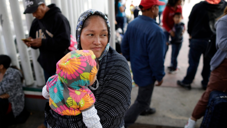 In this June 13, 2018 photo, Maria Rafaela Blancante, of the Mexican state of Michoacan, holds her daughter, Jazmin, as they wait with other families to request political asylum in the United States, across the border in Tijuana, Mexico. (AP Photo/Gregory Bull)