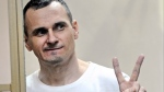 In this Tuesday, Aug. 25, 2015 file photo, Oleg Sentsov gestures from behind bars at a court in Rostov-on-Don, Russia. (AP Photo)