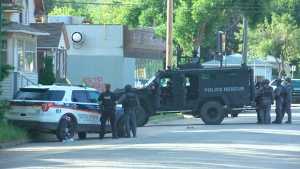 More than 20 Saskatoon police officers, including the tactical support unit, surround a home on Avenue I South. (Levi Mierau/CTV Saskatoon)