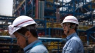 Workers stand near facilities for producing polypropylene at the Sinopec Yanshan Petrochemical Company on the outskirts of Beijing, Friday, May 25, 2018. The facility, part of the Chinese state-owned oil giant Sinopec, opened its doors to journalists on Friday as the U.S. and China continue talks aimed at averting a trade war between the two countries. (AP / Mark Schiefelbein)