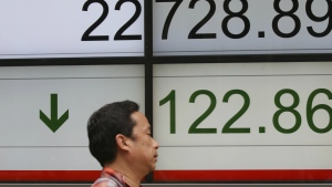 A man walks by an electronic stock board of a securities firm in Tokyo, Monday, June 18, 2018. (AP Photo/Koji Sasahara)
