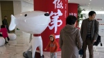 "In this Nov. 11, 2017, photo, a child stands near the mascot for Chinese e-commerce giant JD.com and the words for ""Be Number One"" at the headquarters in Beijing, China. (AP Photo/Ng Han Guan)"