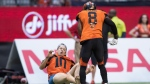 B.C. Lions' Marcell Young (8) knocks down a spectator that ran onto the field of play during the first half of a CFL football game against the Montreal Alouettes in Vancouver, on Saturday June 16, 2018. THE CANADIAN PRESS/Darryl Dyck