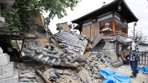 The gate of Myotoku-ji temple collapses after an earthquake hit Ibaraki City, Osaka, western Japan, Monday, June 18, 2018. (Yosuke Mizuno/Kyodo News via AP)