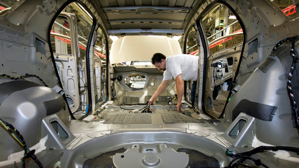 In this Dec. 21, 2006, file photo, an auto worker puts a wiring harness in an empty vehicle body during production of the General Motors' Chevrolet Equinox, Pontiac Torrent and the Suzuki XL7 at the CAMI Automotive facility in Ingersoll, Ontario, Canada. (Dave Chidley/The Canadian Press via AP, File)