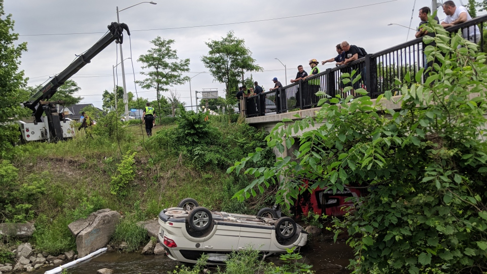 A car flipped into a creek near Bridge and Lancaster streets in Kitchener on Monday, June 18, 2018. (Marta Czurylowicz / CTV Kitchener)