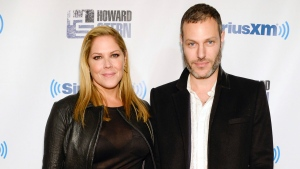 "FILE - In this Jan. 31, 2014 file photo, actress Mary McCormack, left, and husband Michael Morris attend ""Howard Stern's Birthday Bash,"" presented by SiriusXM, at the Hammerstein Ballroom in New York. McCormack has shared video of her husband's Tesla car shooting flames while in Southern California traffic. (Photo by Evan Agostini/Invision/AP, File)"