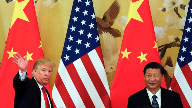 In this Nov. 9, 2017, file photo, U.S. President Donald Trump waves next to Chinese President Xi Jinping after attending a joint news conference at the Great Hall of the People, in Beijing. (AP Photo/Andy Wong)