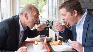 Conservative Leader Andrew Scheer, right, and Saguenay-Le Fjord candidate Richard Martel take a eat poutine at the famous Boivin cheese counter, Thursday, June 14, 2018 in Saguenay Que. (THE CANADIAN PRESS/Jacques Boissinot)