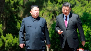 North Korean leader Kim Jong Un, left, and Chinese President Xi Jinping talk while walking in Dalian, China on May 8, 2018. (Korean Central News Agency/Korea News Service via AP)