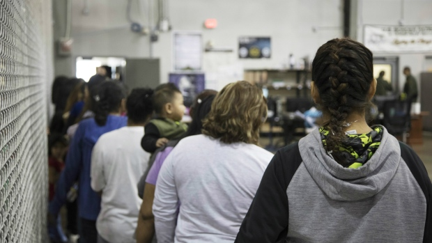 People who've been taken into custody related to cases of illegal entry into the United States, stand in line at a facility in McAllen, Texas, Sunday, June 17, 2018. (U.S. Customs and Border Protection's Rio Grande Valley Sector via AP)
