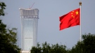 In this Thursday, June 14, 2018, file photo, a Chinese national flag at Tiananmen Square flutters against the capital city tallest skyscraper China Zun Tower under construction at the Central Business District in Beijing. (AP Photo/Andy Wong, File)