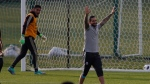 Colombian singer Maluma, right, gesture next to Mexico goalkeeper Jose de Jesus Corona, left, at the end of a training session of the Mexico national soccer team, for the 2018 soccer World Cup, in Moscow, Russia, Tuesday, June 12, 2018. (AP Photo/Eduardo Verdugo)
