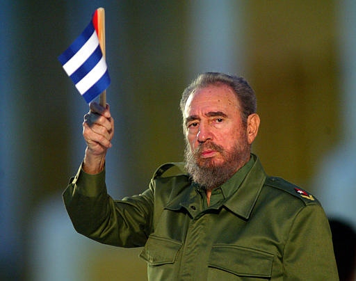 Cuban President Fidel Castro holds a Cuban flag at the beginning of his speech in this Saturday July 26, 2003 file photo in Santiago de Cuba. (AP / Jose Goitia)