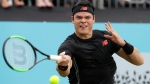 Milos Raonic of Canada plays a return to Yuki Bhambri of India during their singles tennis match at the Queen's Club tennis tournament in London, Tuesday, June 19, 2018. (AP Photo/Kirsty Wigglesworth)