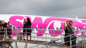 Swoop Airline employees pose for photos next to a Boeing 737 during a media event ahead of their first day of service, Tuesday, June 19, 2018 at John C. Munro International Airport in Hamilton, Ont. THE CANADIAN PRESS/Tara Walton