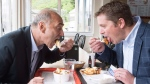 Conservative Leader Andrew Scheer, right, and Saguenay-Le Fjord candidate Richard Martel take a eat poutine at the famous Boivin cheese counter, Thursday, June 14, 2018 in Saguenay Que.THE CANADIAN PRESS/Jacques Boissinot