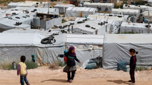Syrian refugee children play at an informal refugee camp, which is seen set between the houses and buildings in Arsal, near the border with Syria, east Lebanon, Wednesday, June 13, 2018. A public spat between the Lebanese government and the United Nation's refugee agency deepened Wednesday as Lebanon's caretaker foreign minister kept up his criticism, accusing the agency of discouraging Syrian refugees from returning home. Lebanon is home to more than a million Syrian refugees, or about a quarter of the country's population, putting a huge strain on the economy. (AP / Hussein Malla)