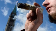 A man smokes a marijuana joint during the annual 4/20 marijuana celebration on Parliament Hill in Ottawa on April 20, 2018. (Canadian Press/Justin Ling)