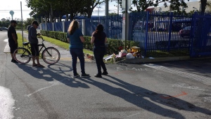 Fans and mourners of rap singer XXXTentacion pause by a memorial, Tuesday, June 19, 2018, outside Riva Motorsports in Deerfield Beach, Fla., where the troubled rapper-singer was killed the day before. (Joe Cavaretta/South Florida Sun-Sentinel via AP)