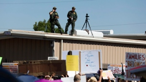 U.S. Border Patrol agents watch as they take photos and video of the crowd protesting outside the U.S. Immigration and Customs Enforcement processing center in El Paso, Texas, Tuesday, June 19, 2018. (Ivan Pierre Aguirre/The San Antonio Express-News)