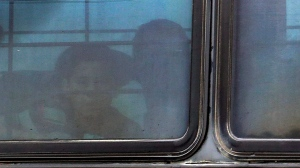 A boy stares out of a heavily tinted bus window leaving a U.S. Customs and Border Protection facility, Tuesday, June 19, 2018, in McAllen, Texas. (AP Photo/Eric Gay)