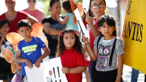Children listen to speakers during an immigration family separation protest in front of the Sandra Day O'Connor U.S. District Court building, Monday, June 18, 2018, in Phoenix. An unapologetic President Donald Trump defended his administration's border-protection policies Monday in the face of rising national outrage over the forced separation of migrant children from their parents. (AP Photo/Ross D. Franklin)