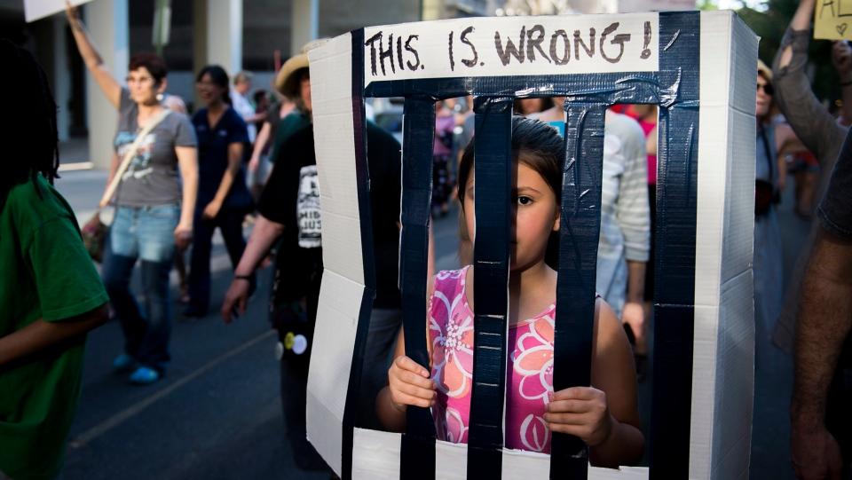 Fiona Pompilio, 10, of Philadelphia marches by Rittenhouse Square as protestors gather near a hotel hosting a GOP fundraiser with Vice President Mike Pence Tuesday, June 19, 2018 in Philadelphia, Pa. The demonstration is a reaction to children being separated from their families by immigration officials. (Joe Lamberti/Camden Courier-Post via AP)