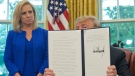 U.S. President Donald Trump holds up an executive order he signed to end family separations, during an event in the Oval Office of the White House in Washington, Wednesday, June 20, 2018. Looking on is Homeland Security Secretary Kirstjen Nielsen, left. (AP / Pablo Martinez Monsivais)