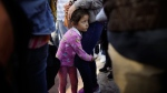 In this June 13, 2018 photo, Nicole Hernandez, of the Mexican state of Guerrero, holds on to her mother as they wait with other families to request political asylum in the United States, across the border in Tijuana, Mexico. (AP / Gregory Bull)
