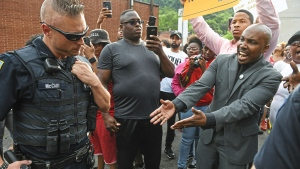 Leonard Hammonds II, of Penn Hills, right, points out that a Turtle Creek Police officer has his hand on his weapon during a rally in East Pittsburgh, Pa. at a protest regarding the shooting death of Antwon Rose by an East Pittsburgh Police officer during a traffic stop the night before on on Wednesday, June 20, 2018. (Steve Mellon/Pittsburgh Post-Gazette)